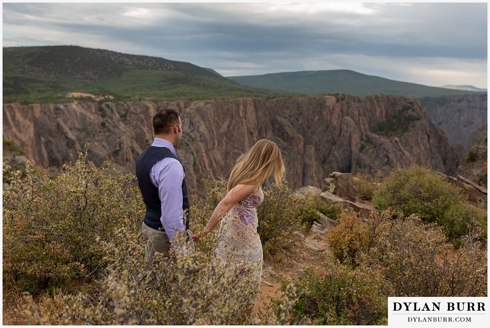 black canyon colorado elopement wedding adventure newlyweds bride and groom walking down to canyon view