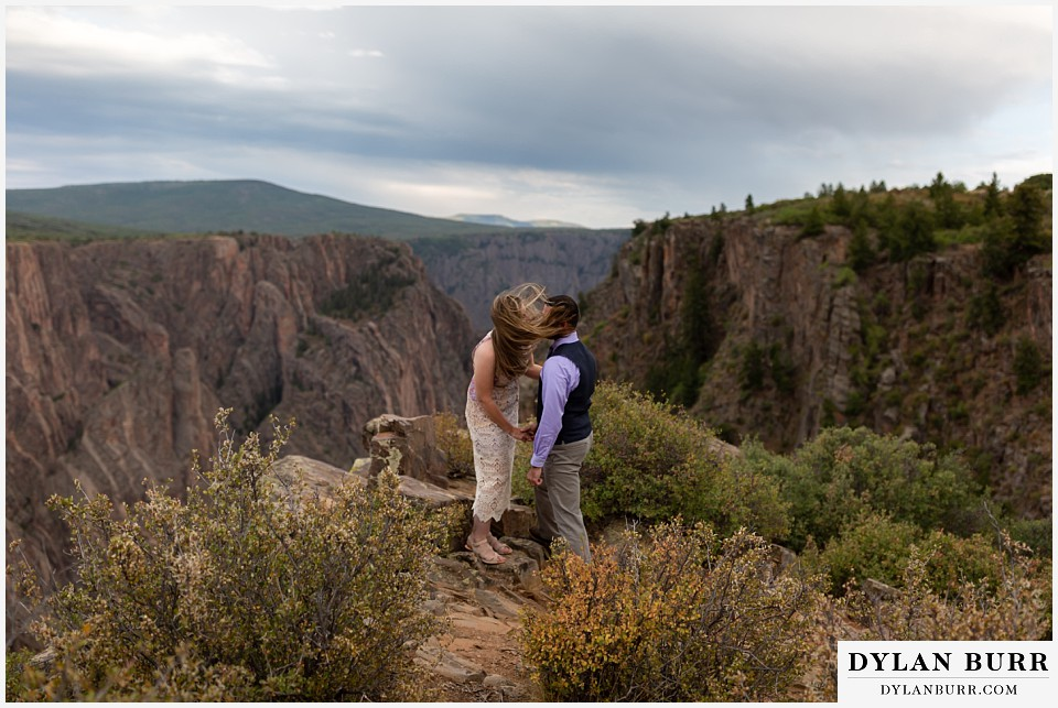 black canyon colorado elopement wedding adventure groom and bride with windswept air
