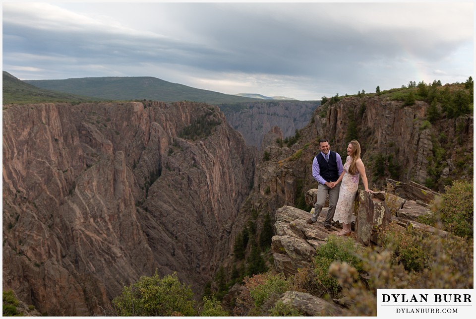 black canyon colorado elopement wedding adventure bride and groom having fun on canyon ledge