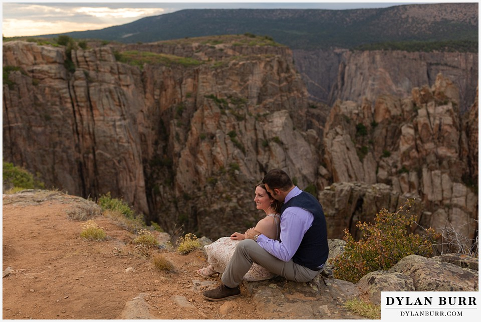 black canyon colorado elopement wedding adventure bride and groom sitting along ledge of canyon