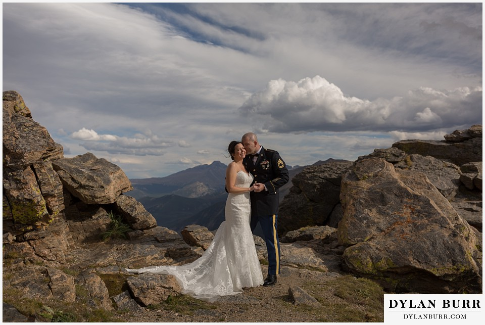 rocky mountain national park wedding bride and groom snuggling on top of the mountains in the sunlight