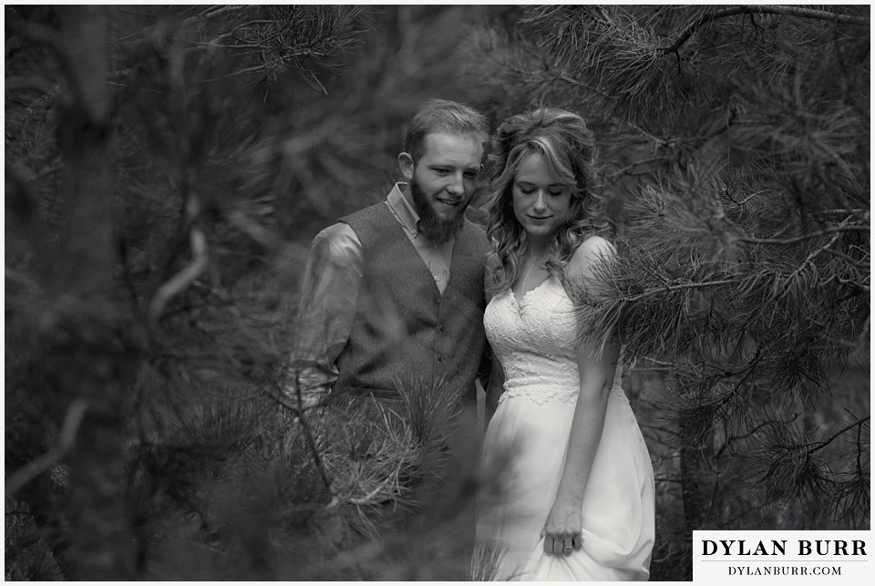 boho backyard colorado wedding black and white photo of bride and groom walking in trees