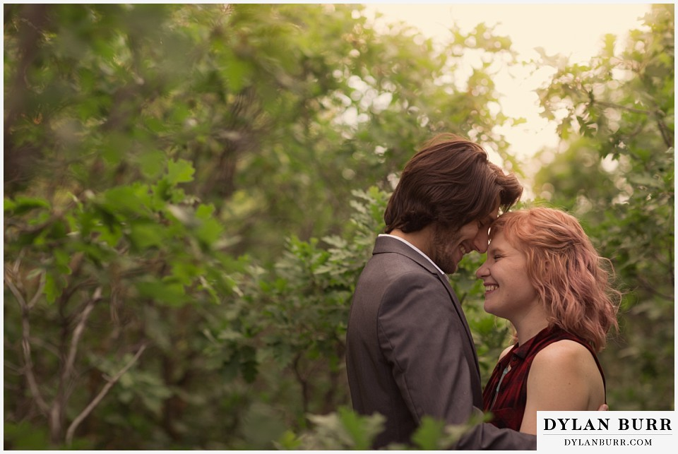 castle rock colorado engagement session snuggles at sunset in oak trees