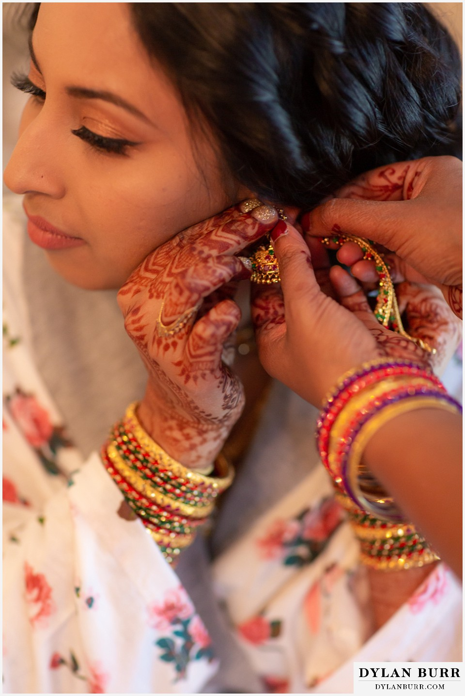 cielo at castle pines wedding colorado mountain wedding close up of henna art on brides hands and putting on earrings