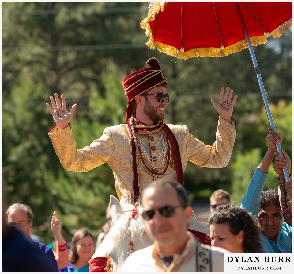cielo at castle pines wedding colorado mountain wedding groom on horse with henna on hands during hindu wedding barat