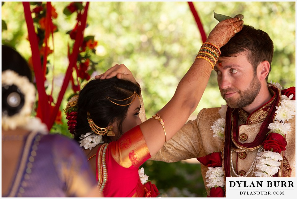 cielo at castle pines wedding colorado mountain wedding bride and groom placing leaves on each other hindu ceremony