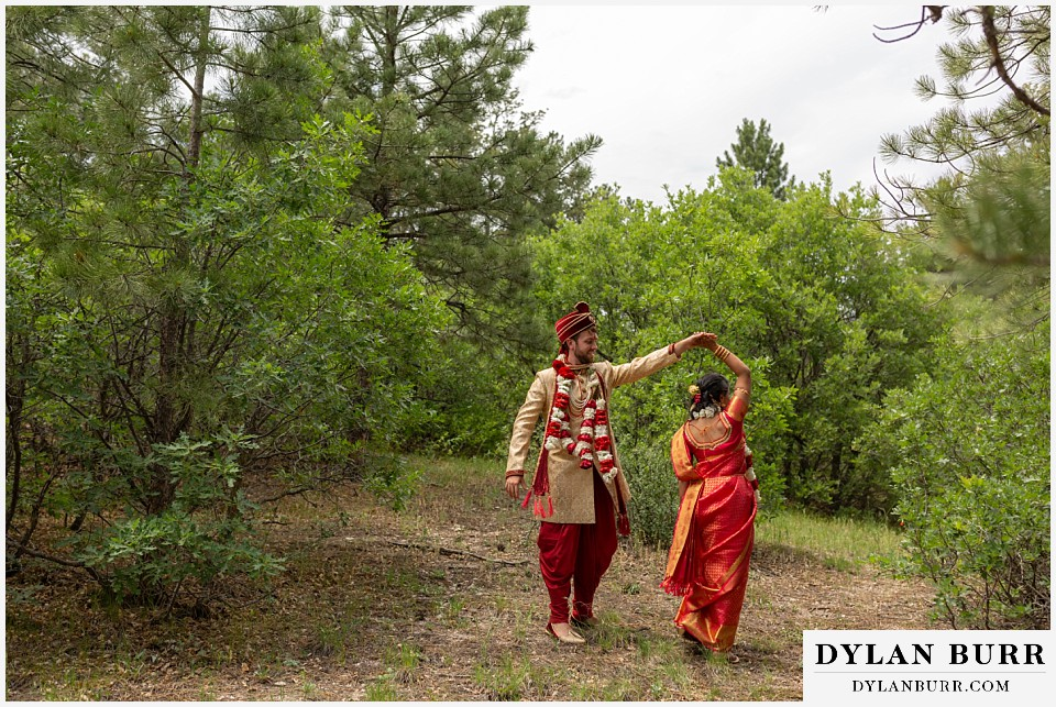 cielo at castle pines wedding colorado mountain wedding hindu bride and groom dancing in a clearing in woods