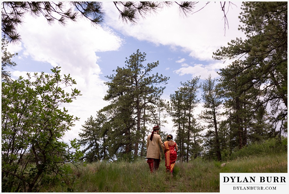 cielo at castle pines wedding colorado mountain wedding hindu wedding newlyweds walking together up hill
