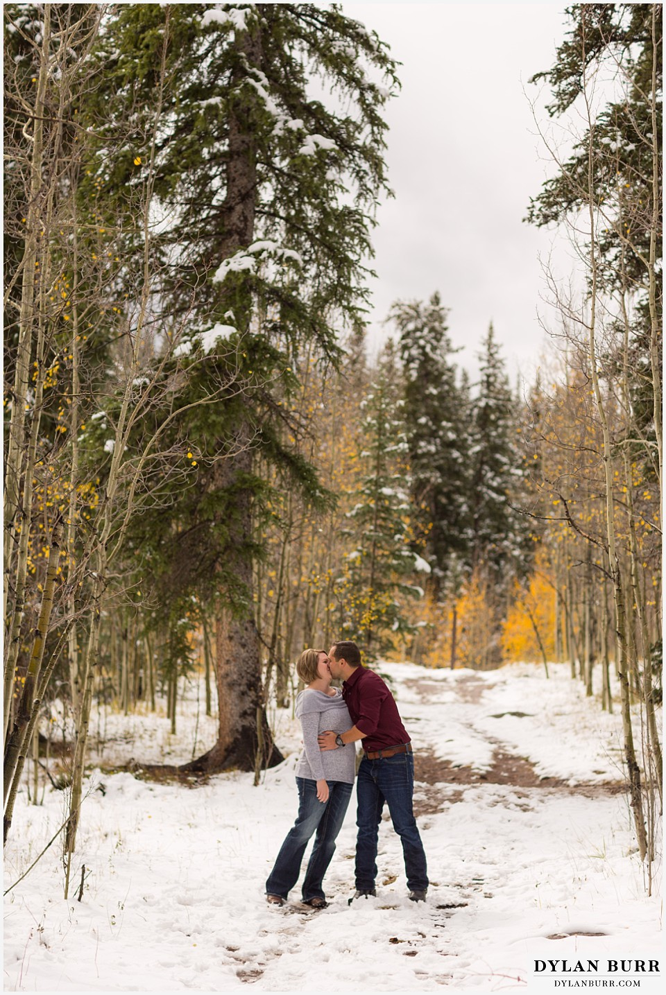 colorado mountain engagement session sharing a kiss in the fall snow