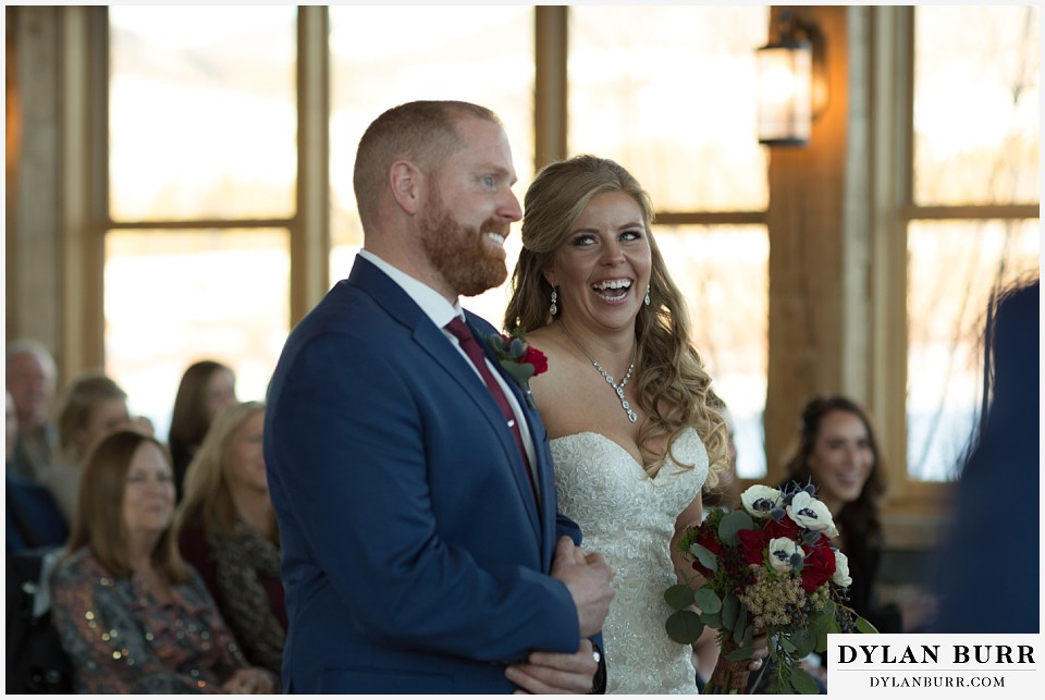 devils thumb ranch wedding in winter  ceremony timber house bride laughing