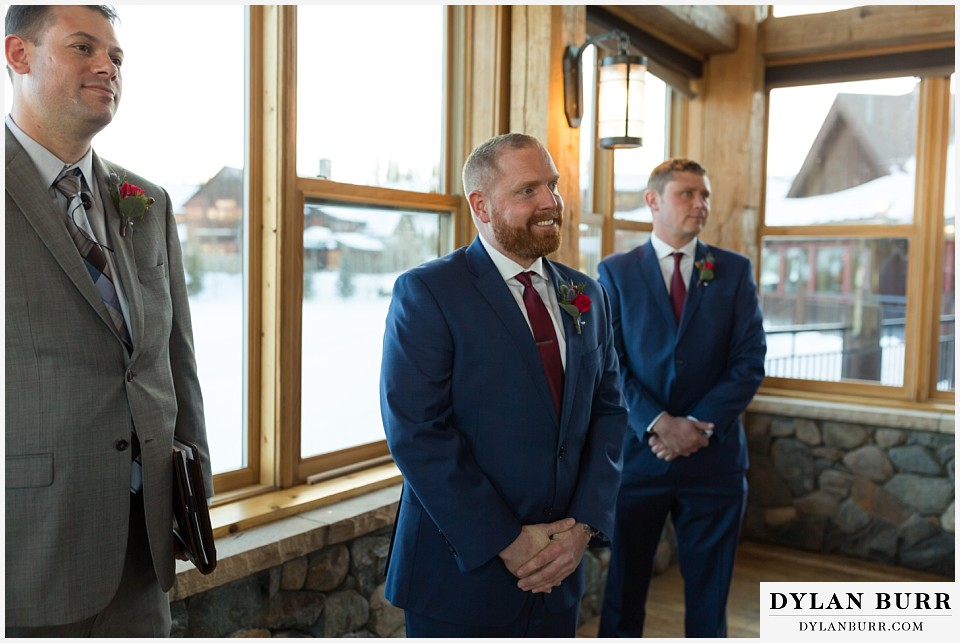 devils thumb ranch wedding in winter ceremony timber house excited groom
