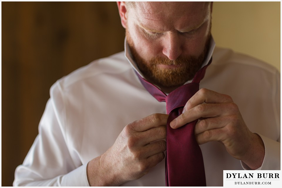devils thumb ranch wedding in winter groom tying tie