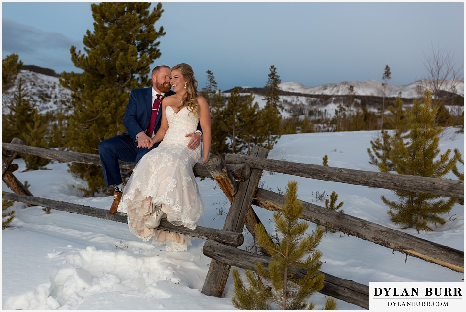 devils thumb ranch wedding in winter newlyweds sitting on fence