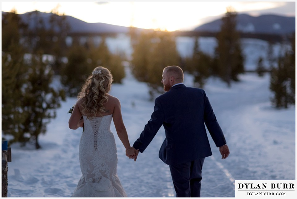 devils thumb ranch wedding in winter newlyweds walking into sunset