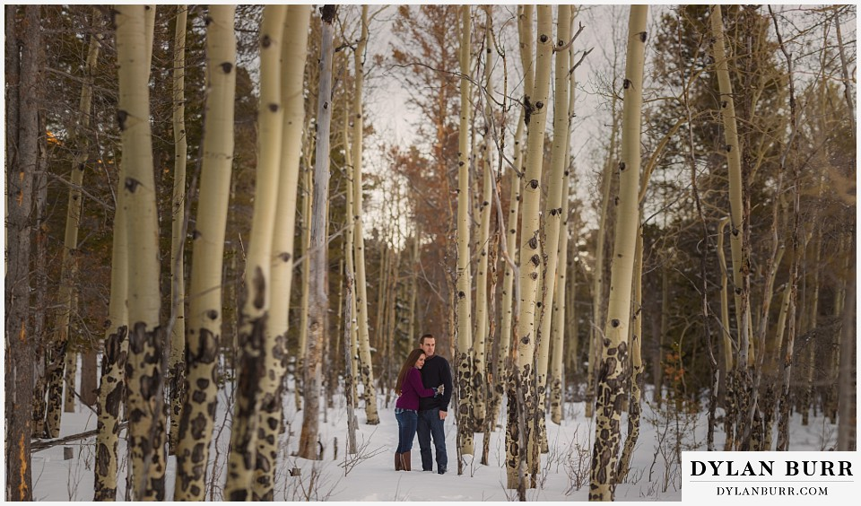 how to prepare for my engagement session couple standing in snow in aspen trees