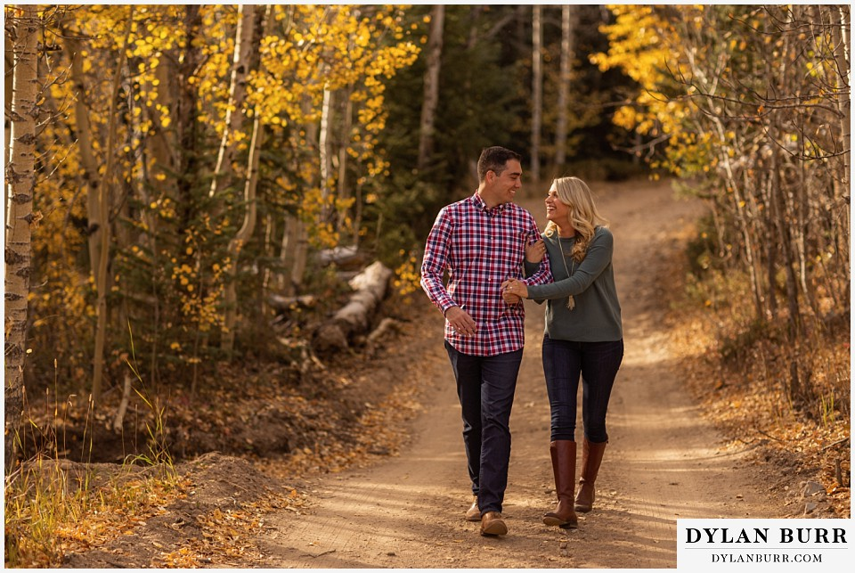 how to prepare for my engagement session couple walking together on road in the fall