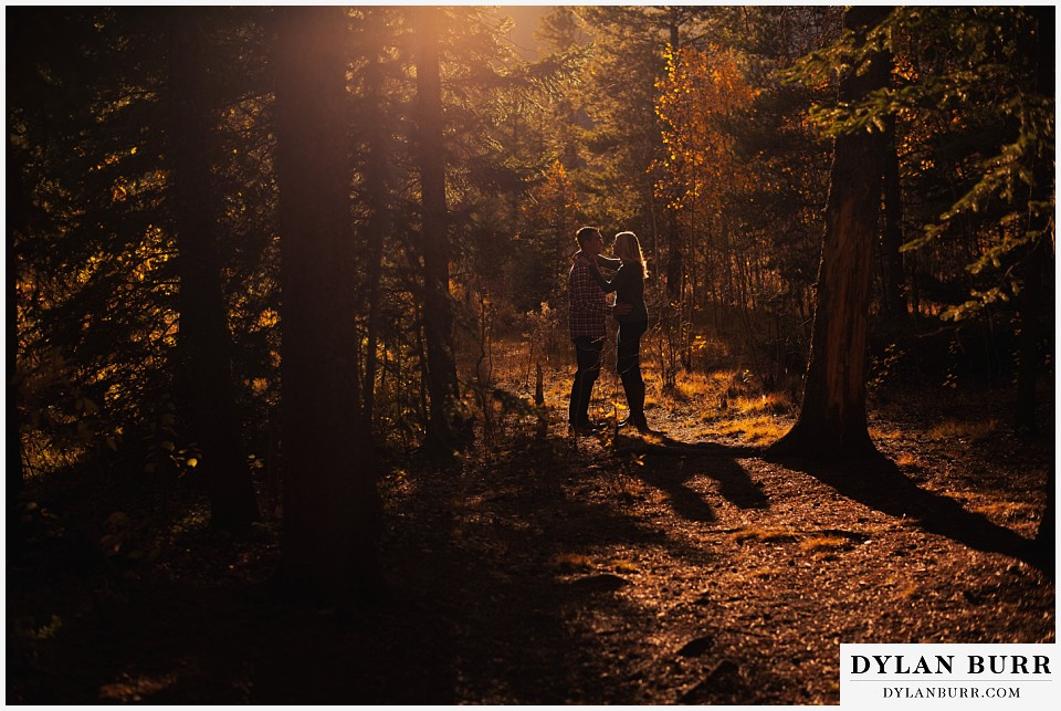 how to prepare for my engagement session couple standing in pine trees at sunset