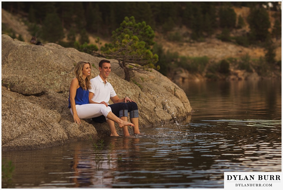 how to prepare for my engagement session couple sitting on rock near lake playing in water