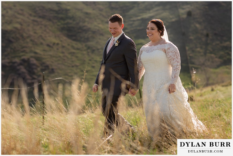 mother cabrini shrine wedding golden colorado bride and groom walking together in mountain meadow