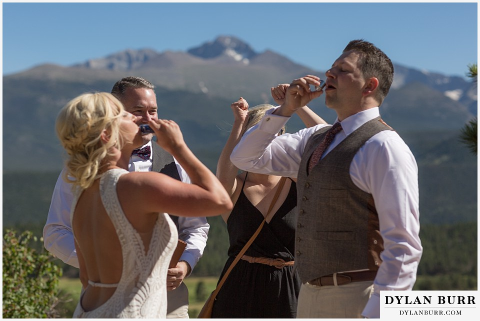 rocky mountain national park wedding elopement bride and groom celebrating with a shot of whiskey