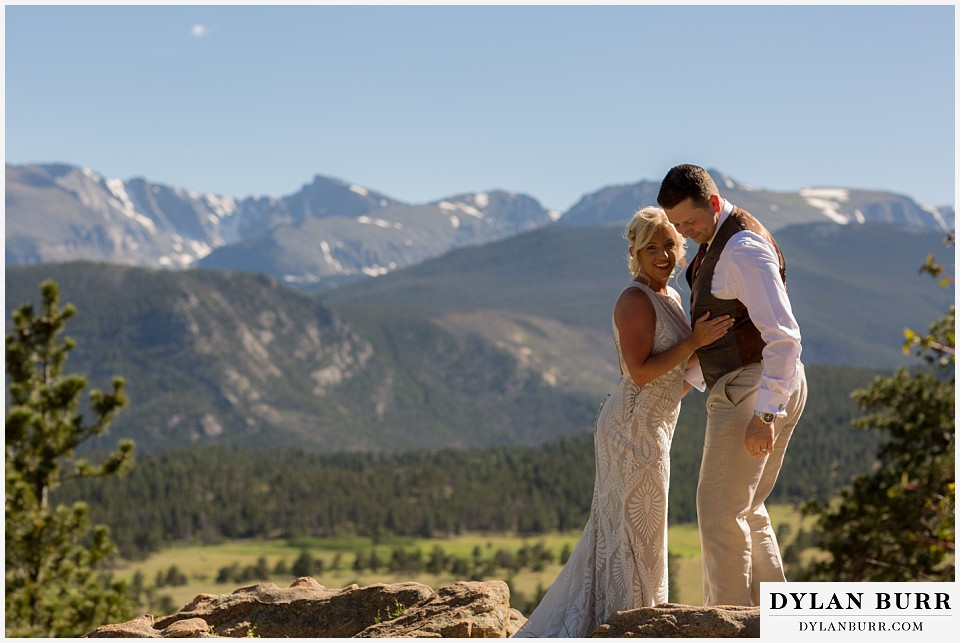 rocky mountain national park wedding elopement happy just married bride and groom standing on rock ledge