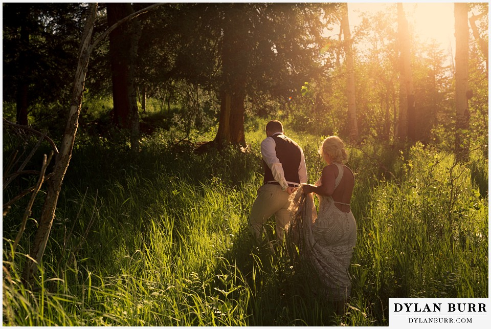 rocky mountain national park wedding elopement bride groom walking in tall grass in sunlight