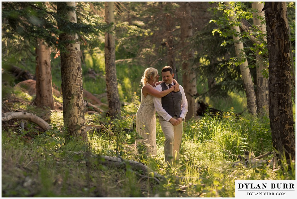 rocky mountain national park wedding elopement bride and groom standing in forest with sunlit glow