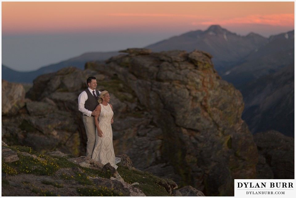 rocky mountain national park wedding elopement bride and groom watching the sunset from the top of the mountains in the wind