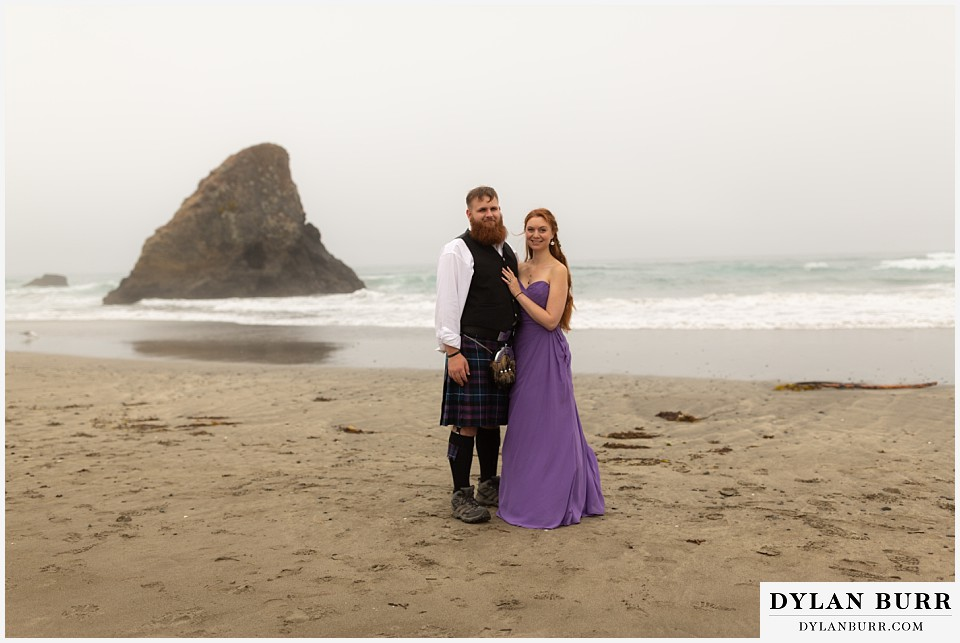 santa cruz california elopement wedding adventure maid of honor and best man with sharkfin rock in background at beach