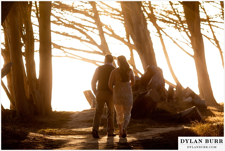 santa cruz california elopement wedding adventure bride and groom walking into sunlight and cypress trees