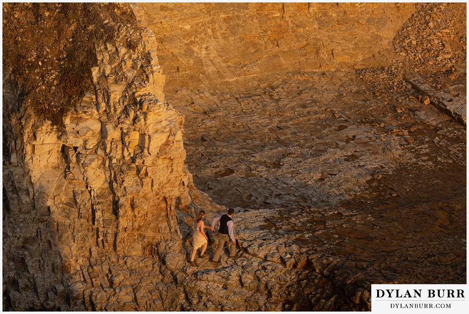 santa cruz california elopement wedding adventure bride and groom walking together on rock cliffs at sunset