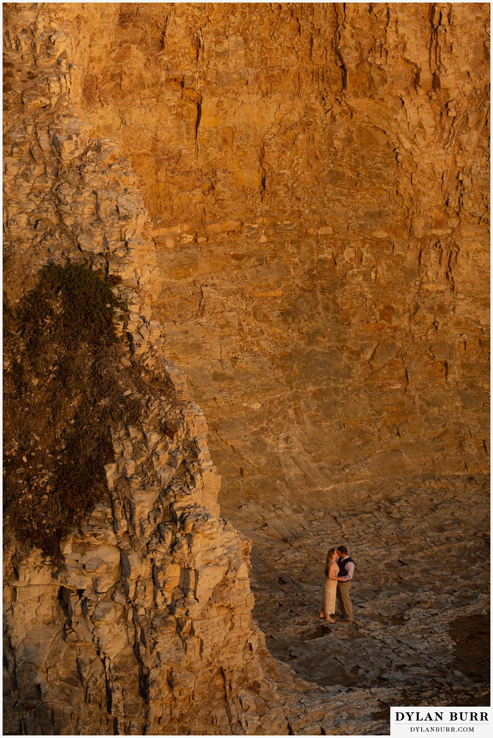 santa cruz california elopement wedding adventure bride and groom as base of cliffs at sunset
