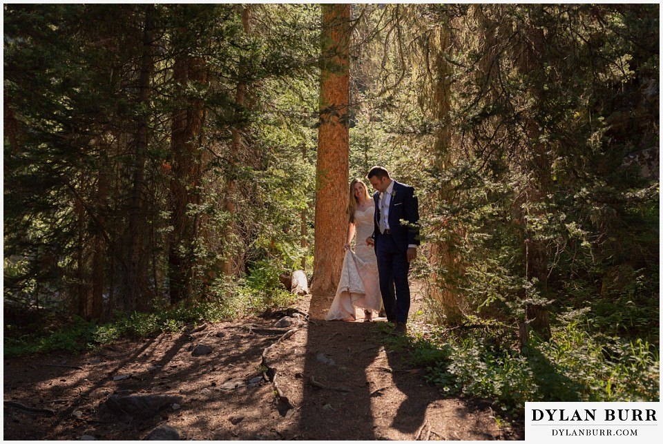 uncompahgre national forest colorado elopement wedding adventure bride and groom walking in the light between pine trees