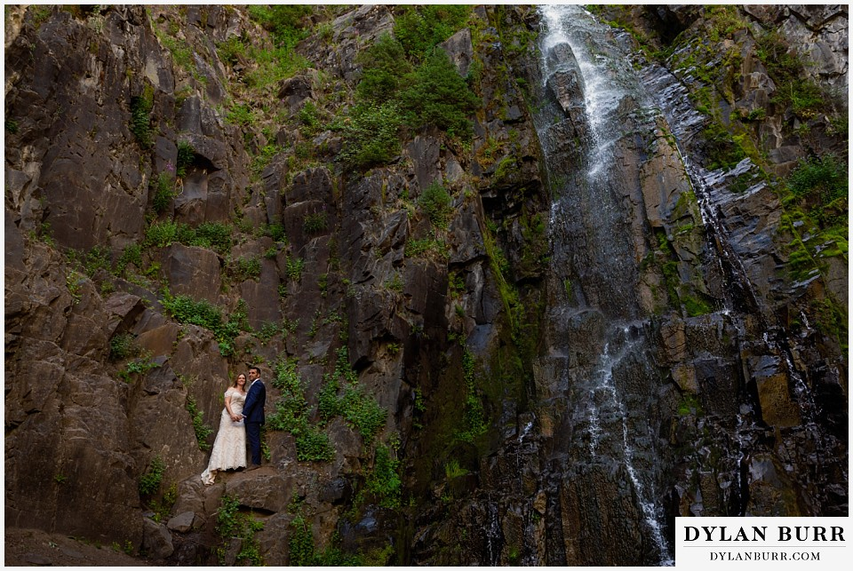 uncompahgre national forest colorado elopement wedding adventure bride and groom wide shot with couple standing on rock wall