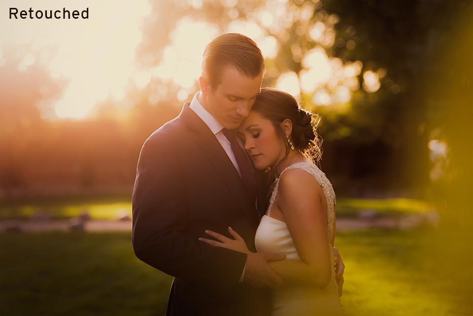 newlywed couple standing together in glowing light at sunset